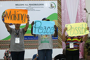MPI Training Participants holding signs Making Peace Possible