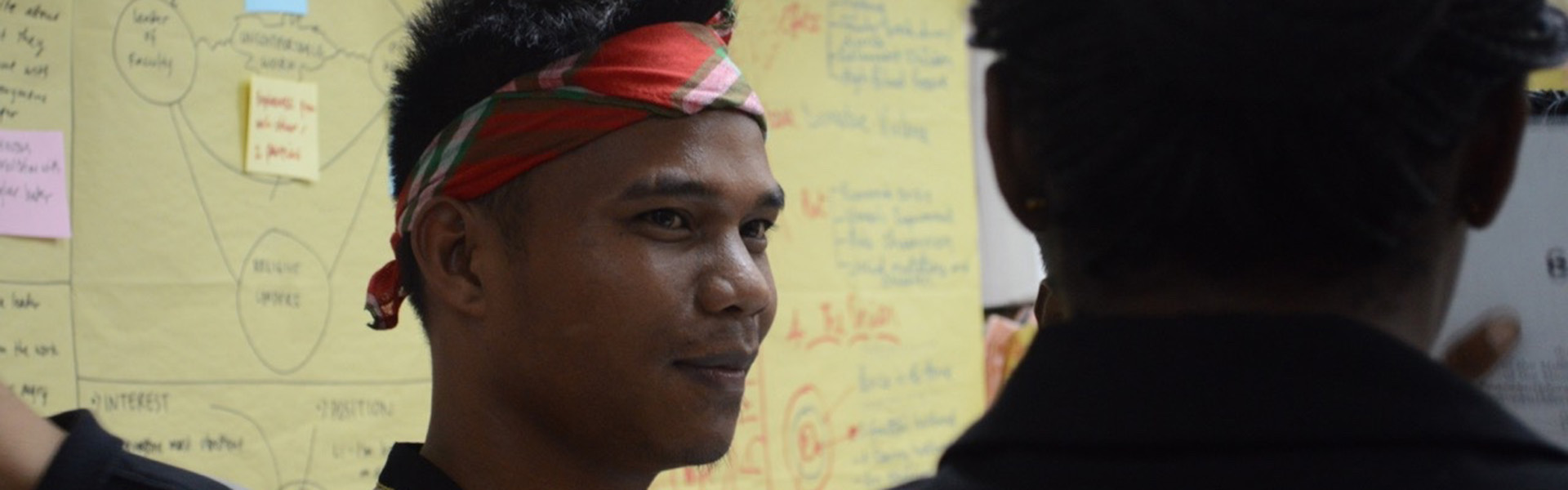 Gebert Andang wearing tribal head scarf in classroom at MPI training