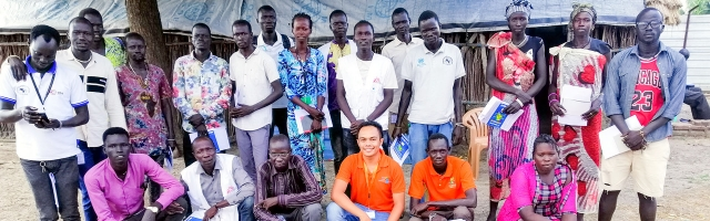 Nohman with local peacebuilders in South Sudan outside and posing for picture