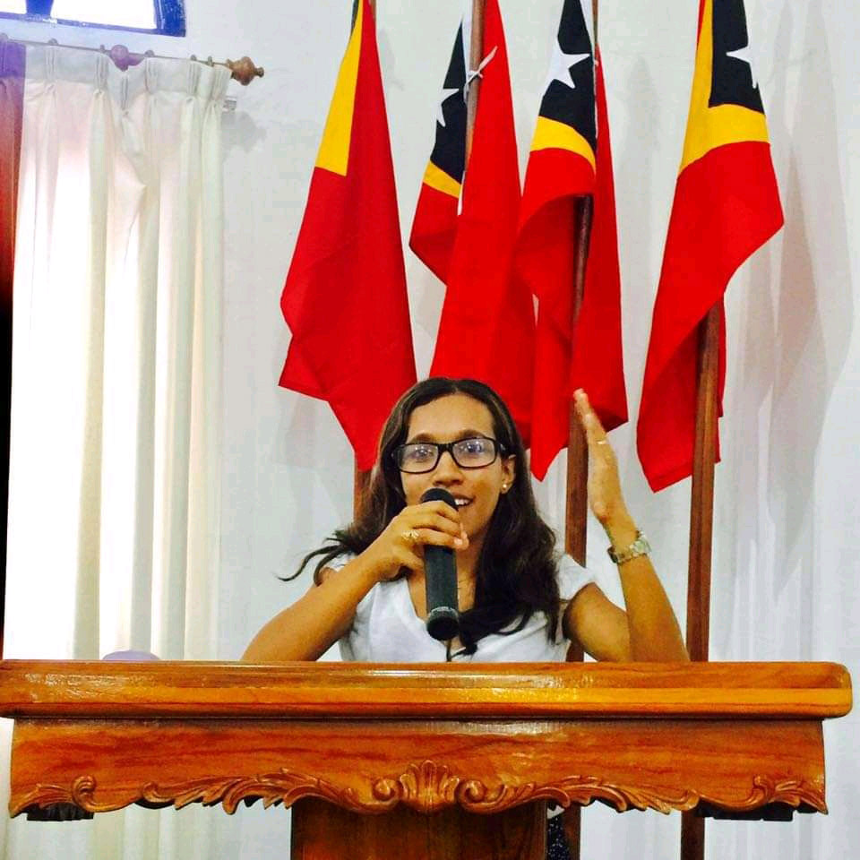 Tecla giving a talk in front of Timorese flags